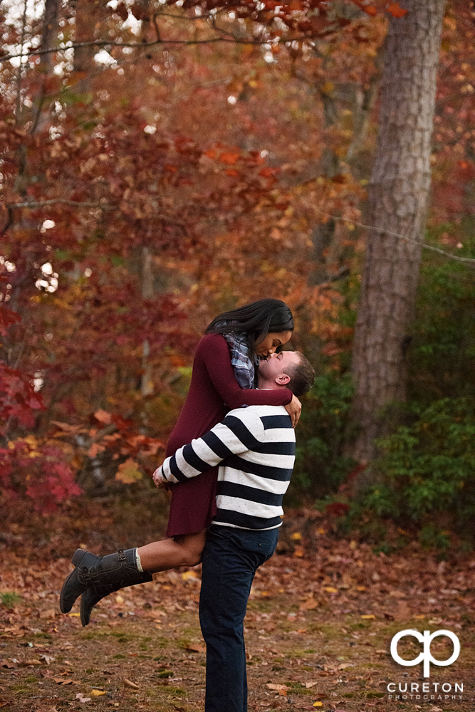 Groom lifting his fiancee with a backdrop of fall colors during their engagement session.