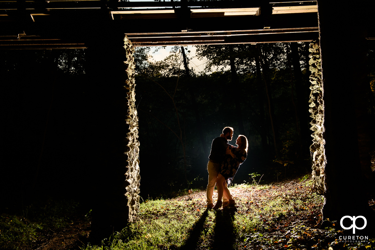 Engaged couple dancing in the woods.