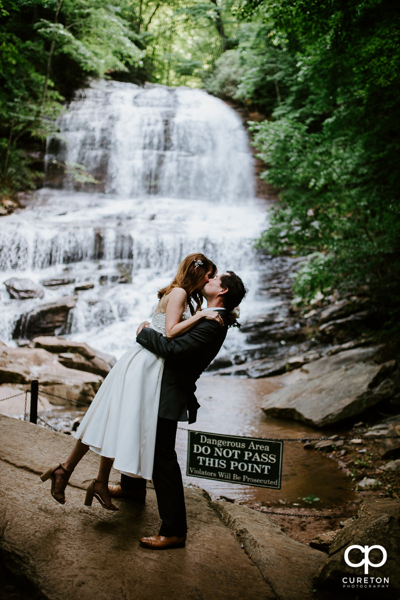 Groom lifting his bride in front of the waterfall after their wedding at Pearson's Falls in Saluda,NC.