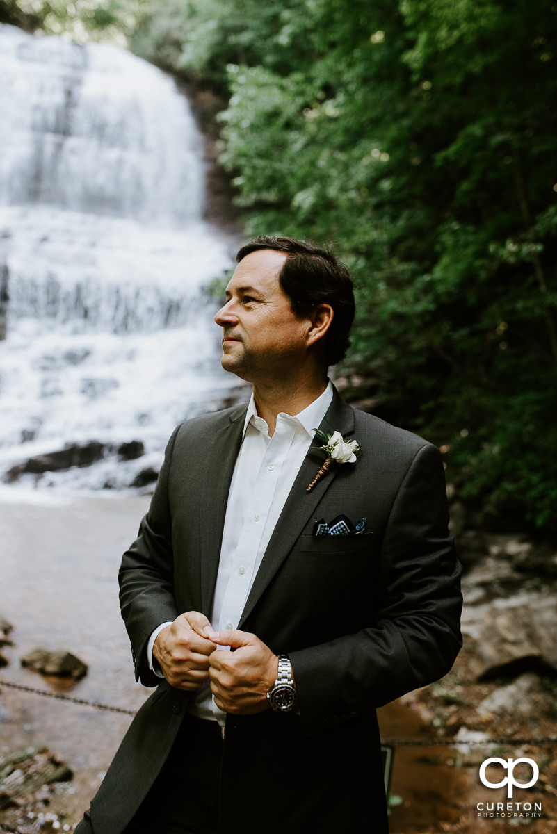 Groom in front of a waterfall.