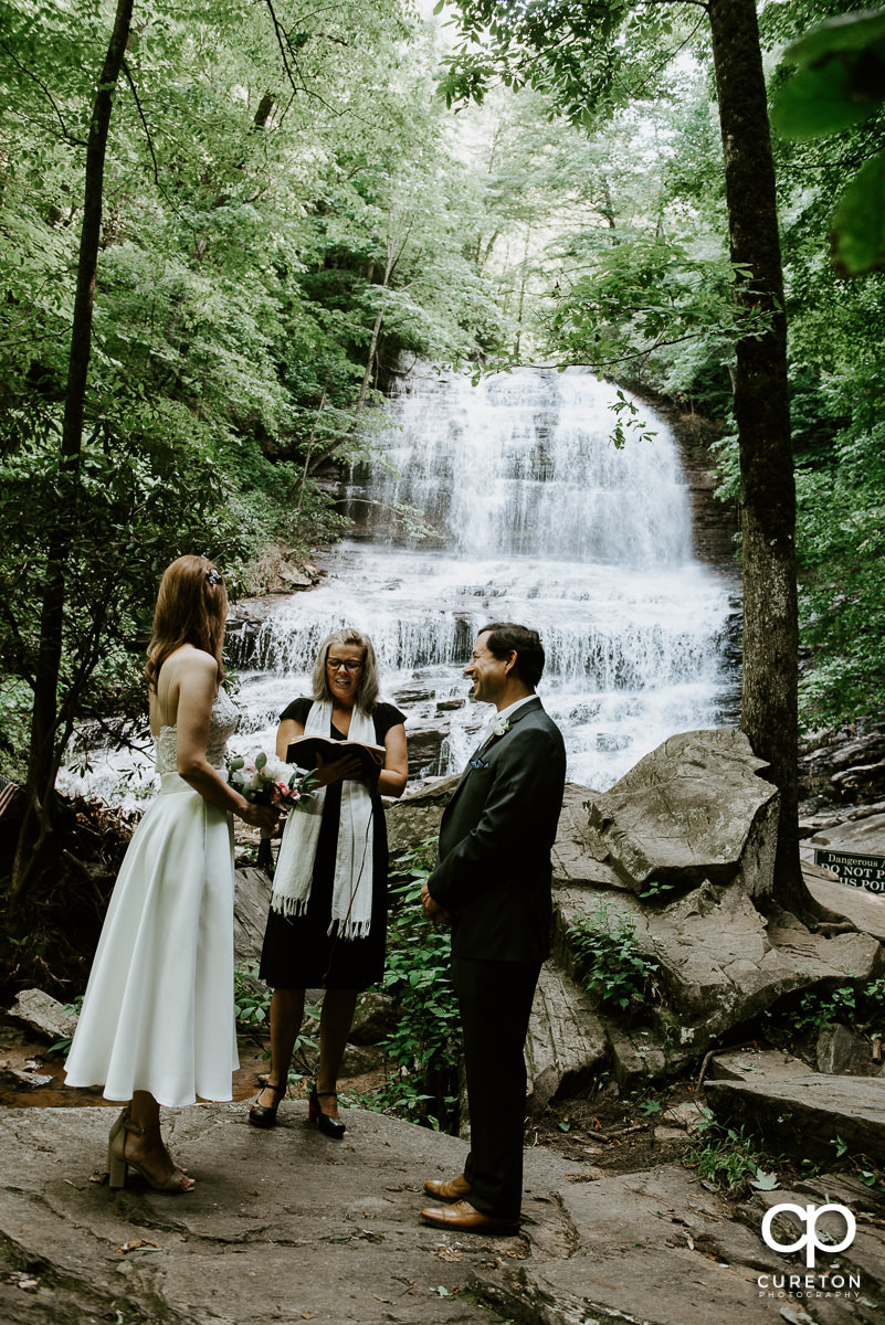 Bride and groom getting married underneath a waterfall at Pearson's falls in Saluda,NC.