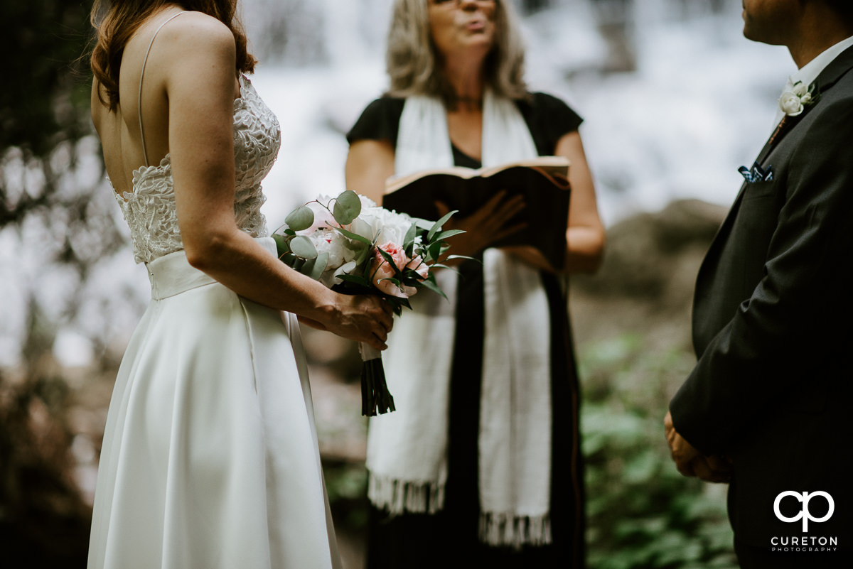 Bride holding a beautiful bouquet in the forest.