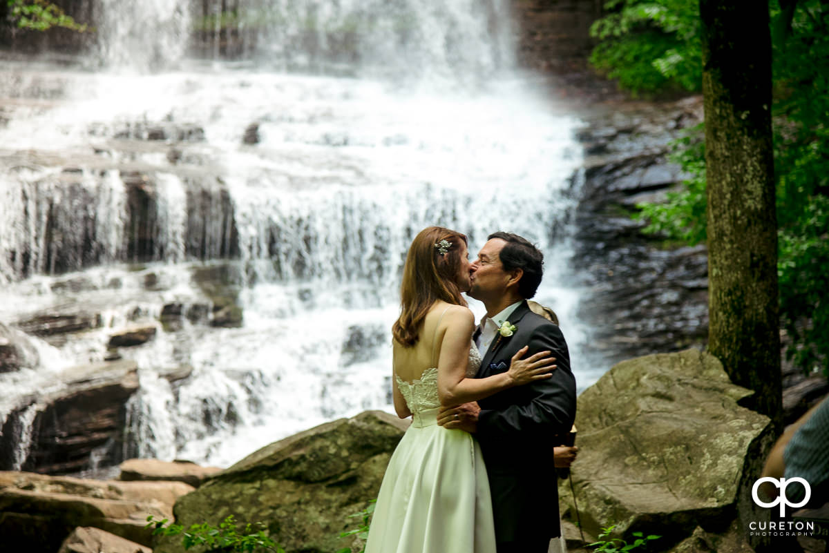 Bride and groom first kiss at the waterfall wedding in North Carolina.