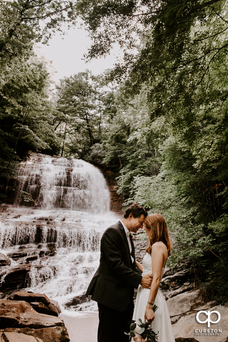 Married couple in front of a waterfall after an elopement wedding.