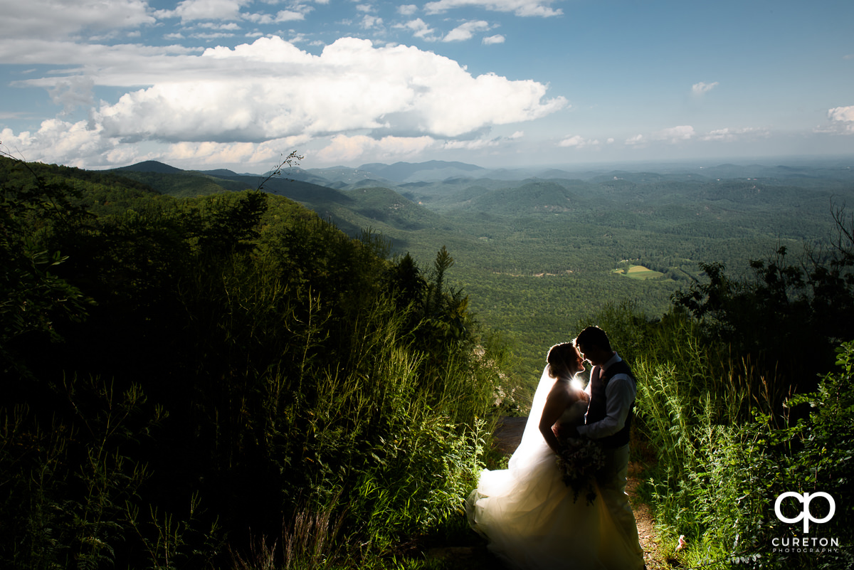 Bride and groom on a cliff after their Pretty Place wedding in the mountains.