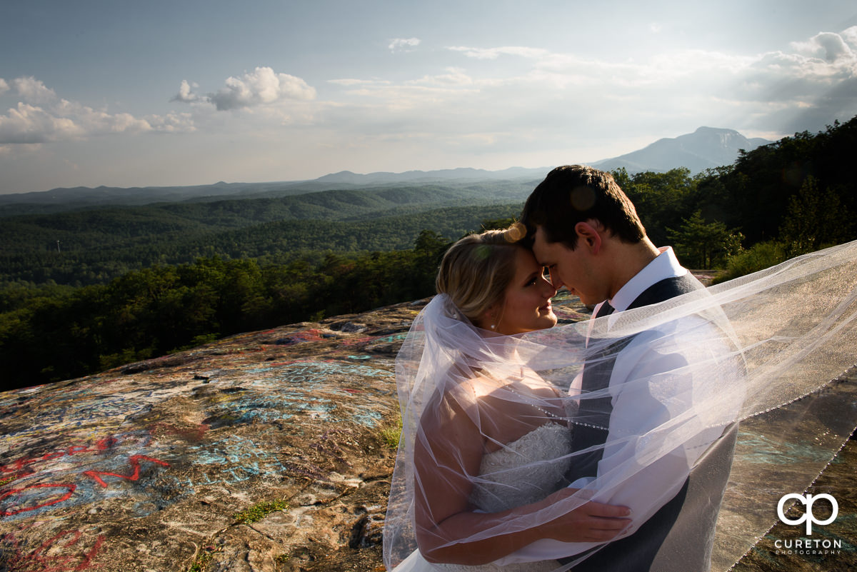 Bride and Groom at Bald Rock on a cliff with the veil blowing in the wind.