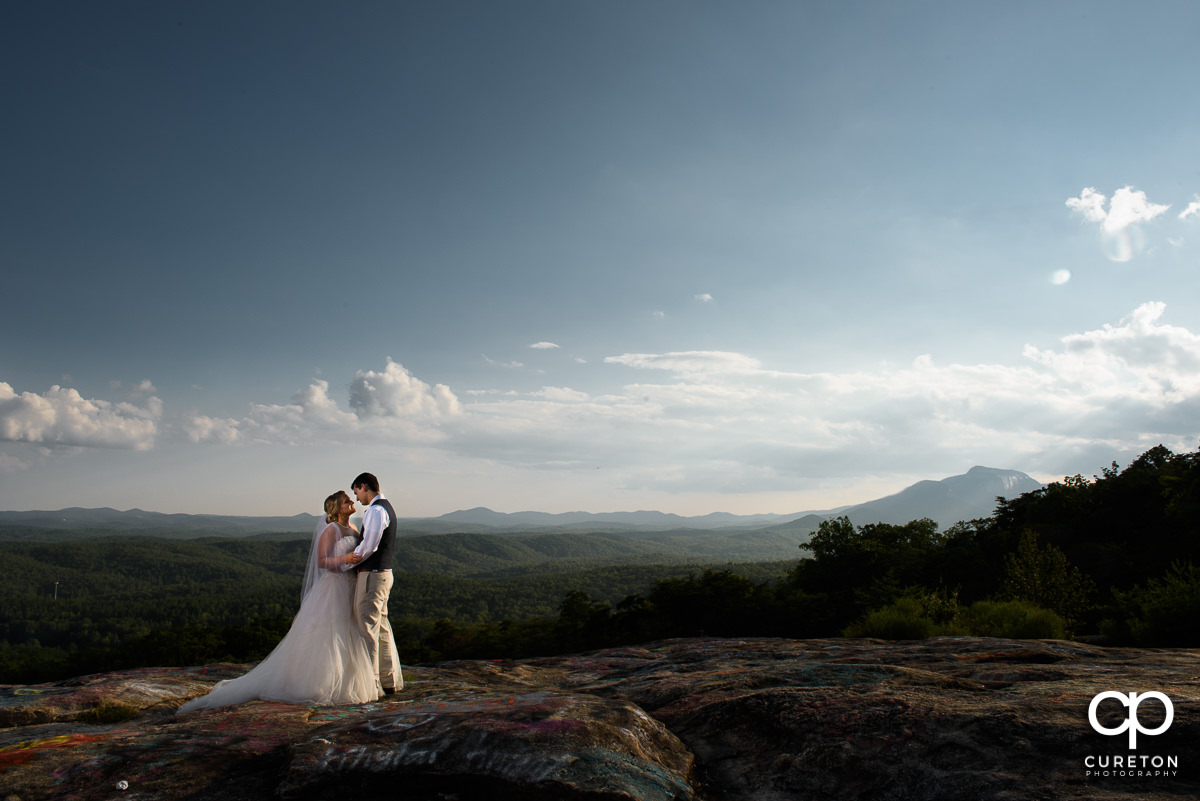 Bride and Groom on a cliff with the mountains in the background.