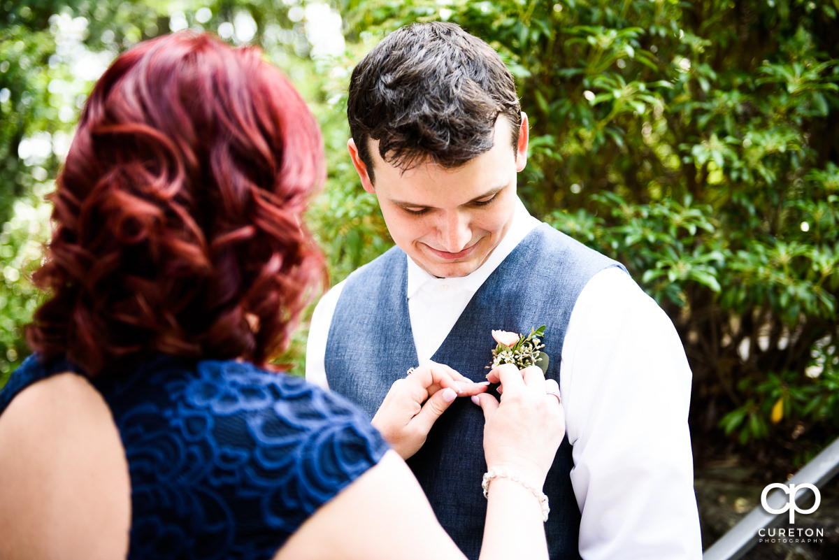 Groom getting his boutonniere on.