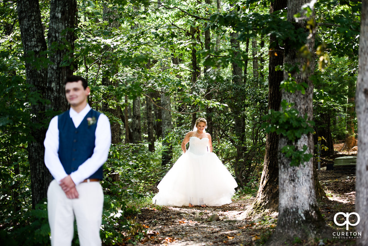 Bride walking up behind the groom before their first look at Pretty Place.