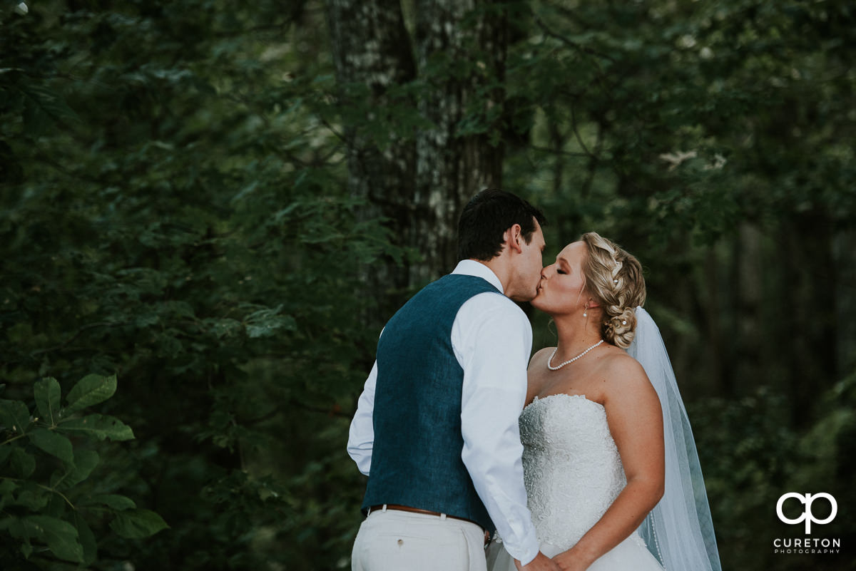 Groom and bride kissing during their first look.