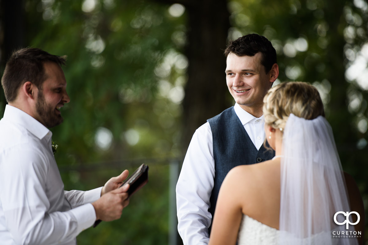 Groom smiling during the ceremony.