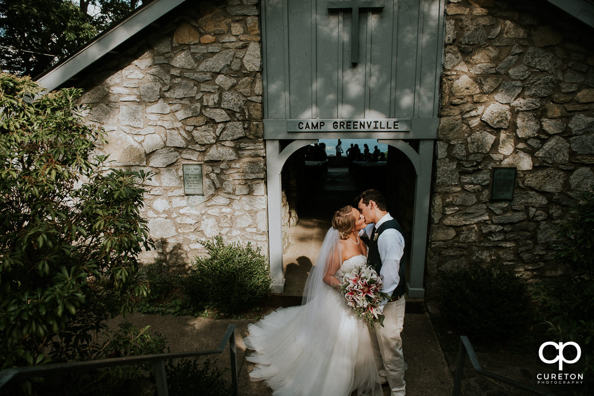 Bride and groom kissing at the doorway of Symmes Chapel after their wedding ceremony.