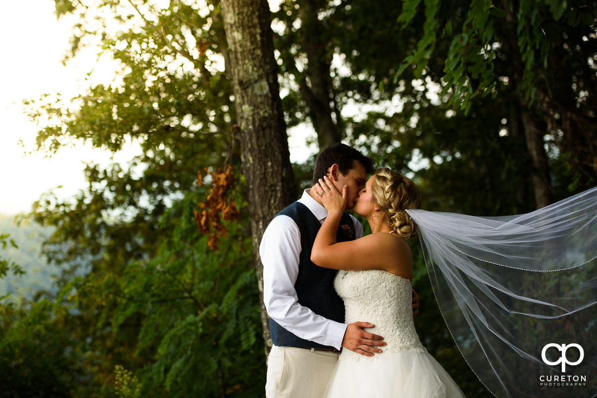 Bride holding groom as her veil blows in the breeze.