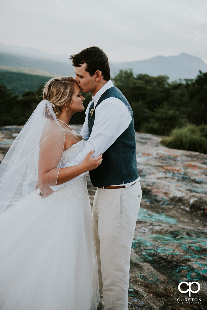 Bride and groom hugging on Bald Rock in the mountains of South Carolina.