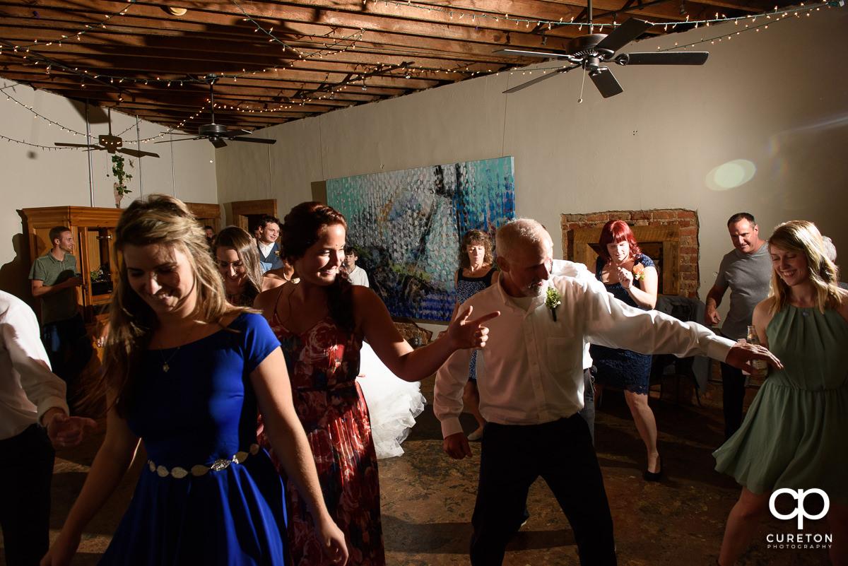 Wedding reception guests dancing at Artisan Traders.
