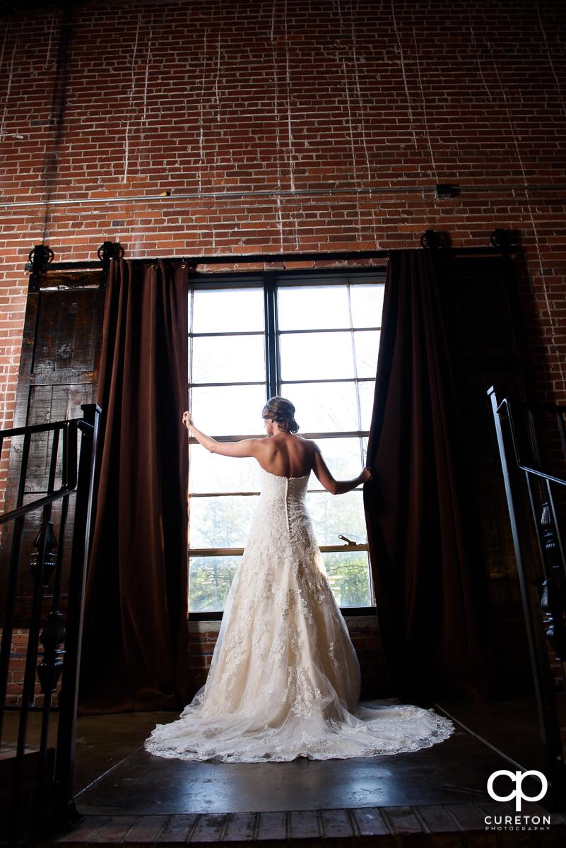 Bride standing in the window.