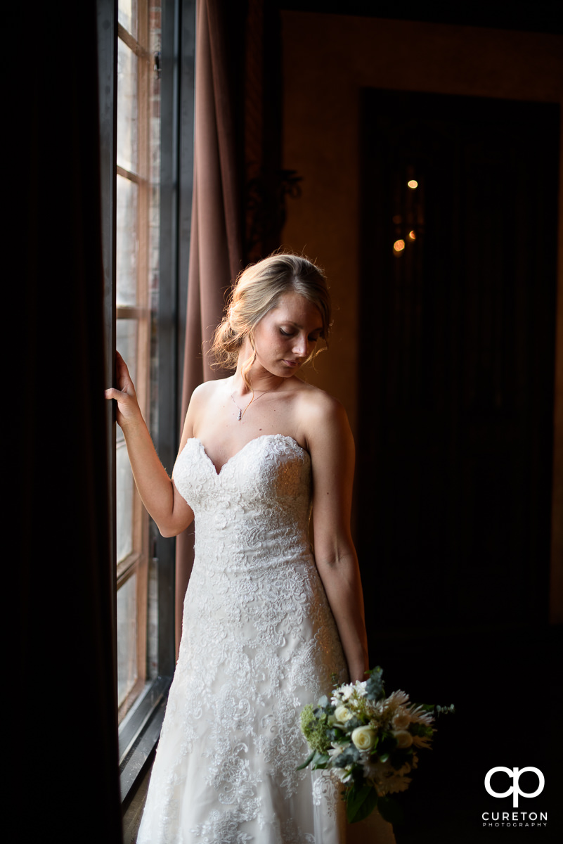 Bride holding her bouquet down while standing in perfect window light.