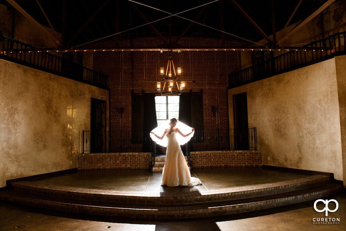 Bride holding her veil out while backlit in the main hall at Revel Event Center for her bridal session.