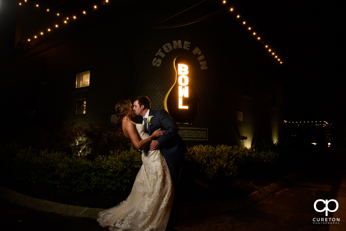 Groom dipping the bride in front of the Stone Pin Bowling sign their Revel Event Center wedding in Greenville,SC.
