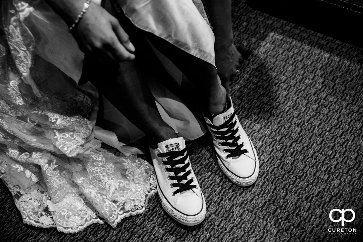 Bride putting on her Chuck Taylor Converse shoes.