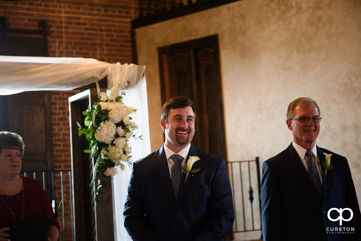 Groom smiling as he sees his bride for the first time.