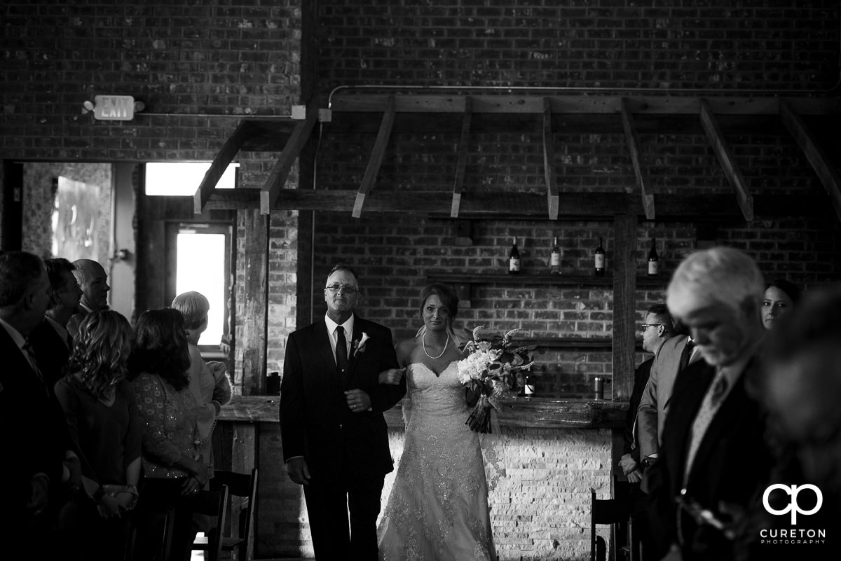 Bride walking down the aisle with her dad crying.