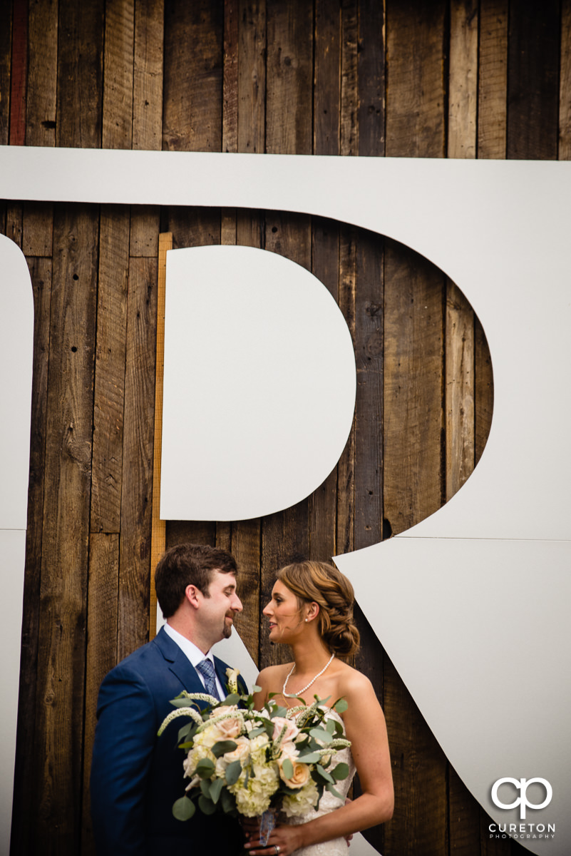 Bride and groom standing underneath a giant letter R.