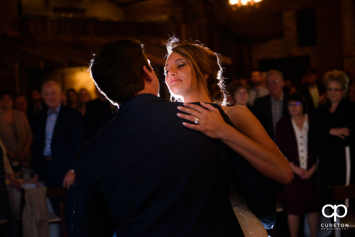Bride smiling at her husband during their first dance.