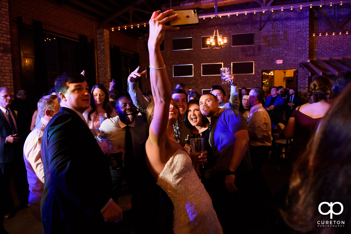 Bride taking a selfie with her wedding guests during the reception.