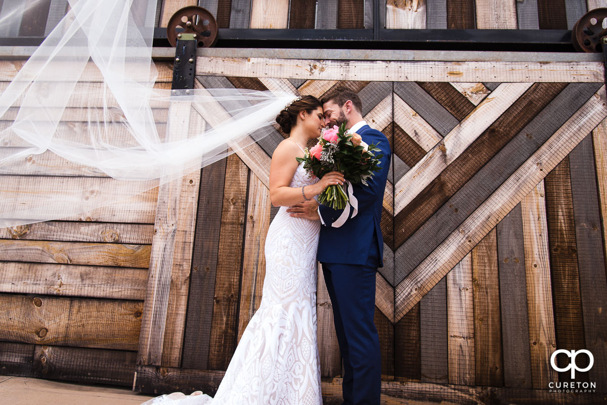 Bride and groom hugging as her veil blows into the wind before their wedding at Revel Event Center in Greenville,SC.