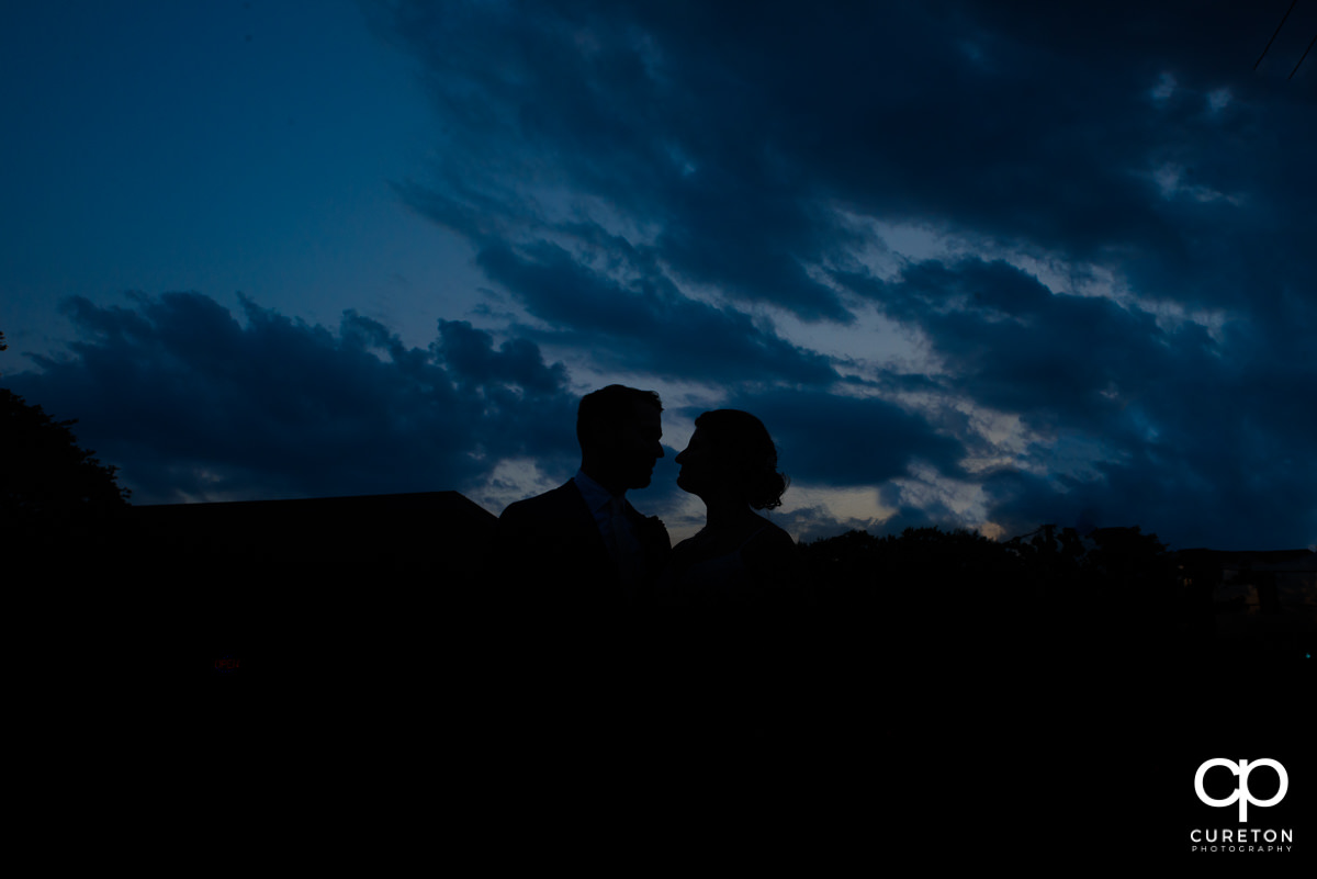 Bride and groom silhouette with deep blue sky before their wedding at Revel Event Center in Greenville,SC.