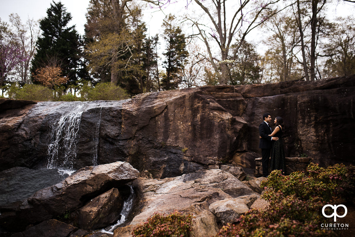 Future bride and groom hugging in front of a waterfall at their engagement session at The Rock Quarry Garden and Cleveland Park in Greenville,SC.