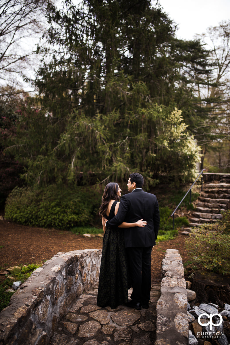 Nicely dressed engaged couple walking over a stone bridge at their engagement session at The Rock Quarry Garden and Cleveland Park in Greenville,SC.