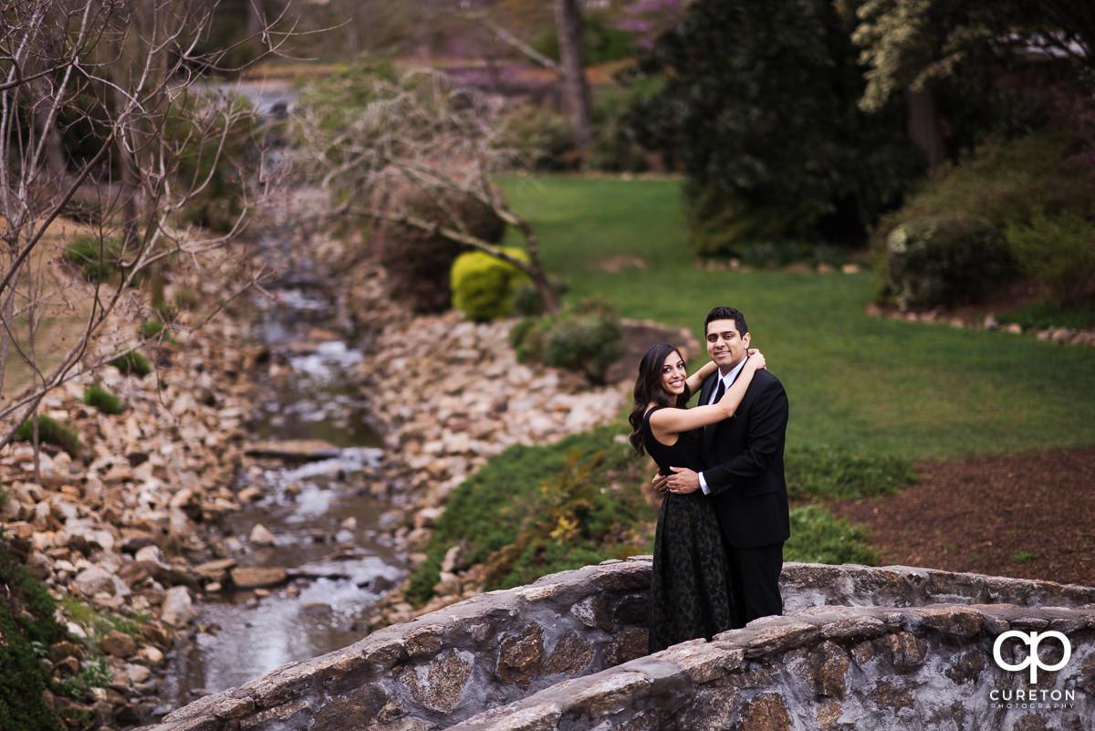 Engaged couple walking on a stone bridge.