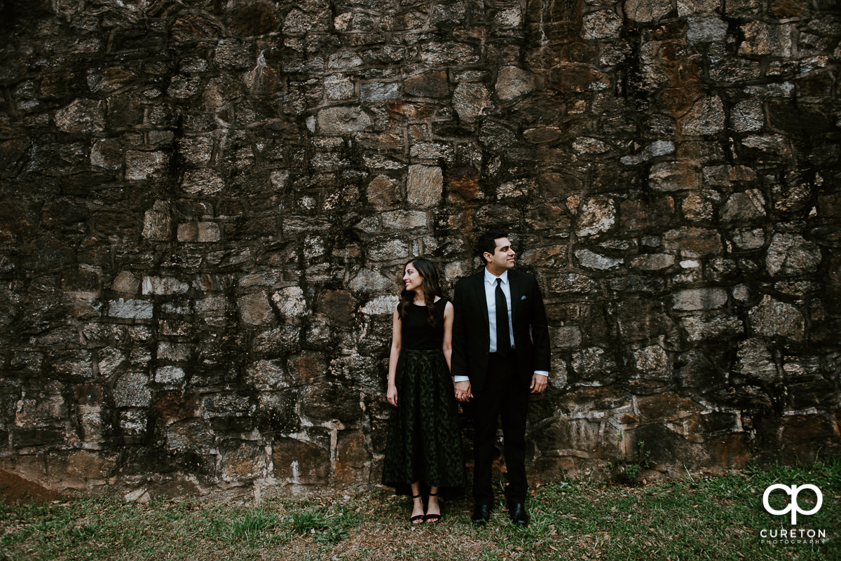 Man and woman standing on a stone wall at their engagement session at The Rock Quarry Garden and Cleveland Park in Greenville,SC.
