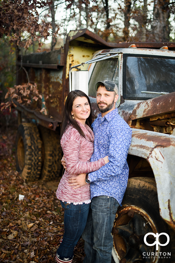 Engaged couple standing near an old rusted truck during their Blue Ridge engagement session.