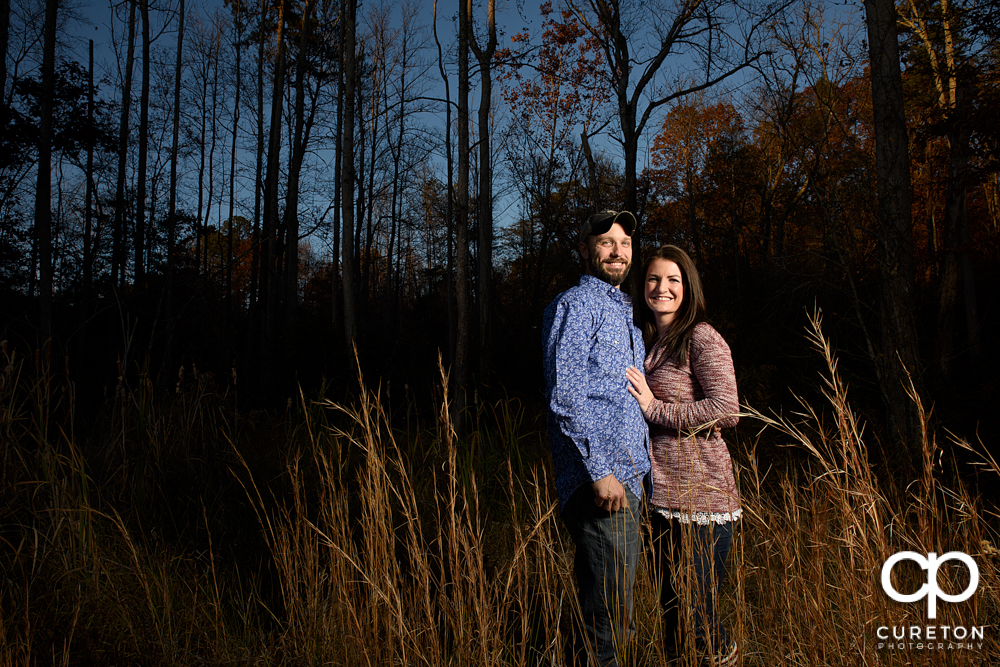 Engaged couple in a field.