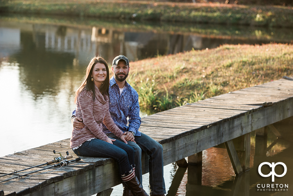 Future bride and groom sitting on a dock.