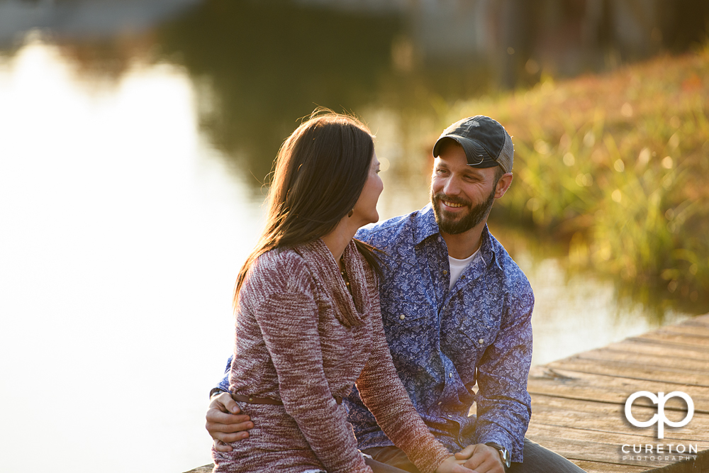 Engaged couple looking at each other on a dock.