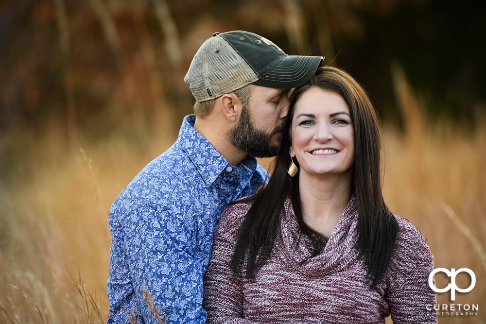 Engaged couple standing in tall grass during their engagement session in Blue Ridge.