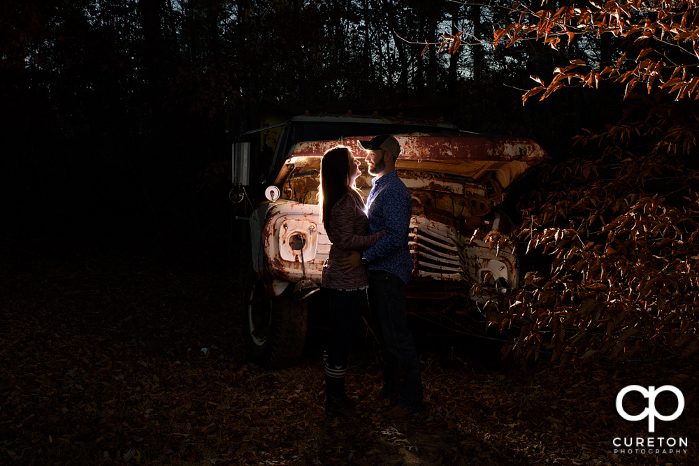 Engaged couple near a rusted truck.