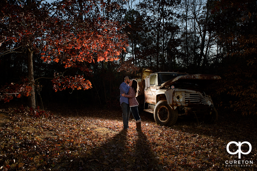 Engaged couple kissing in the fall leaves.