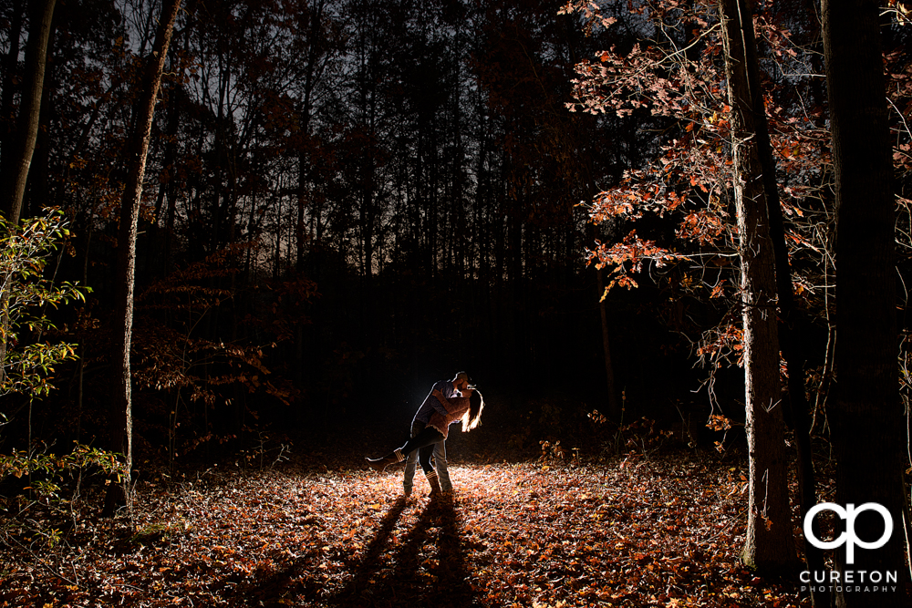 Engaged couple dipping in the forest during their fall Blue Ridge engagement session.