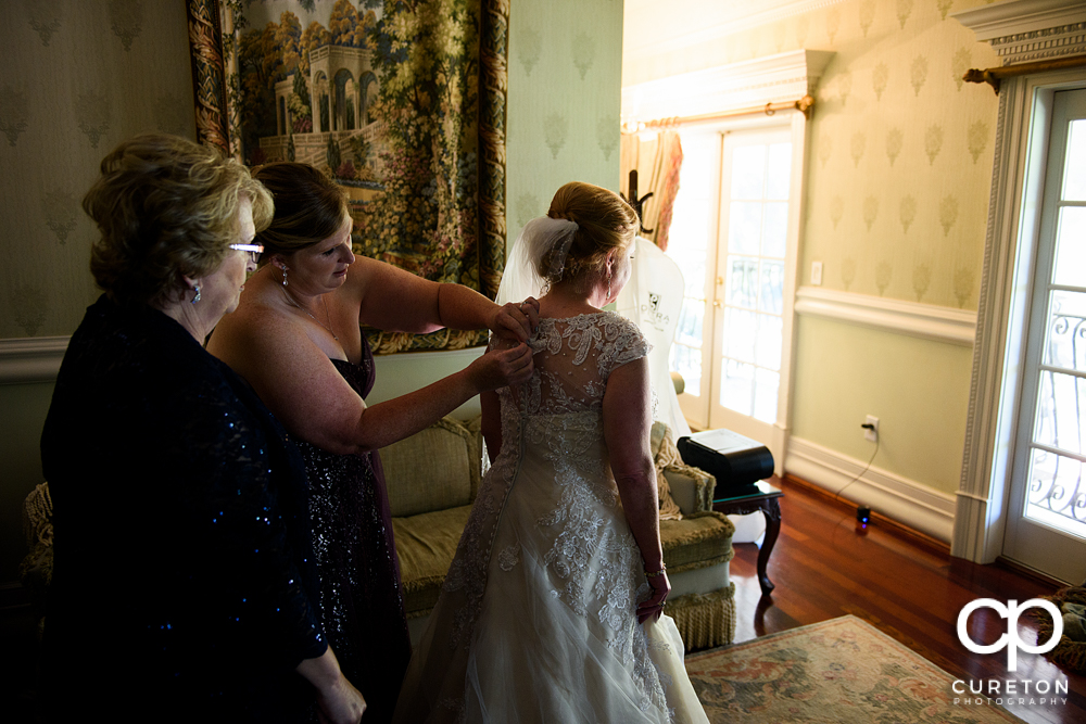 The bride being helped into her dress in the bridal suite of the Ryan Nicholas Inn.