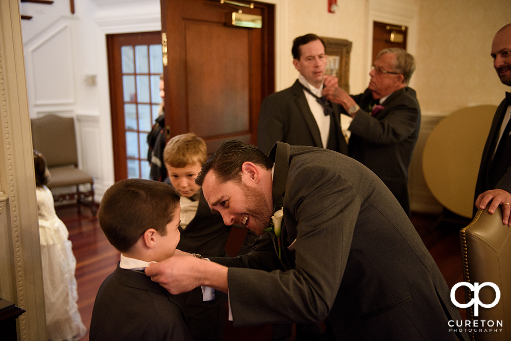 The groom helping his son with the tie.
