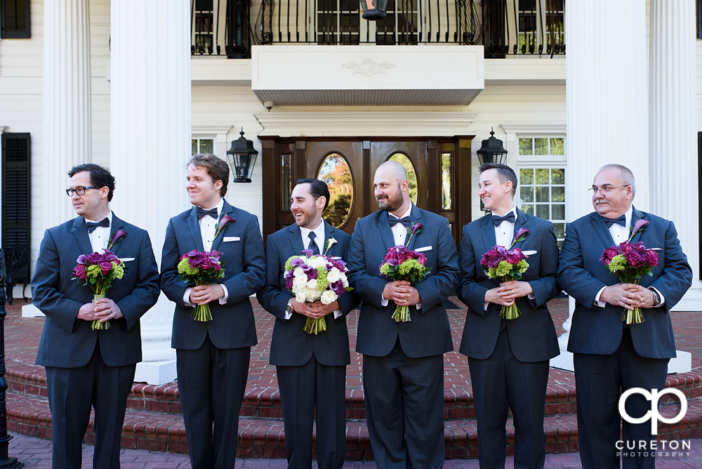 The groomsmen holding the bridesmaids' flowers