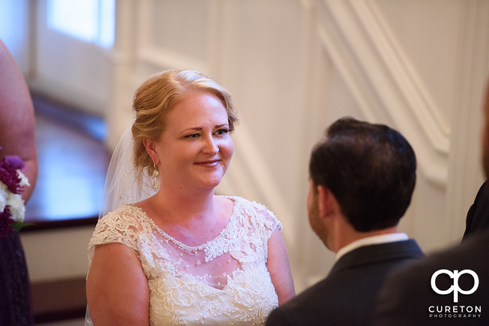 Bride smiling at the groom during the ceremony.