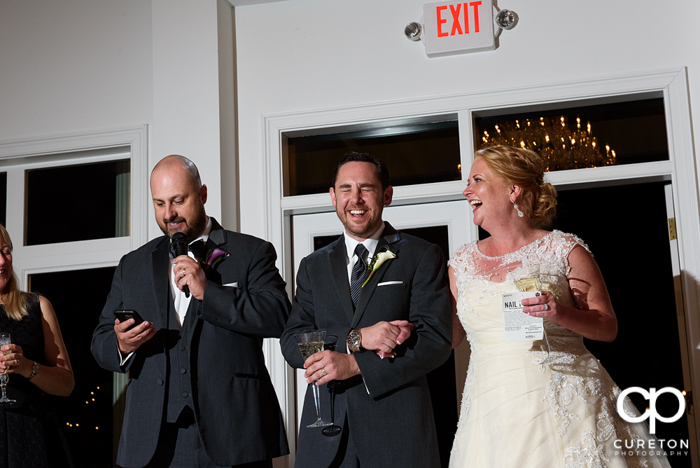 The bride and groom listen as the maid of honor and best man give a toast