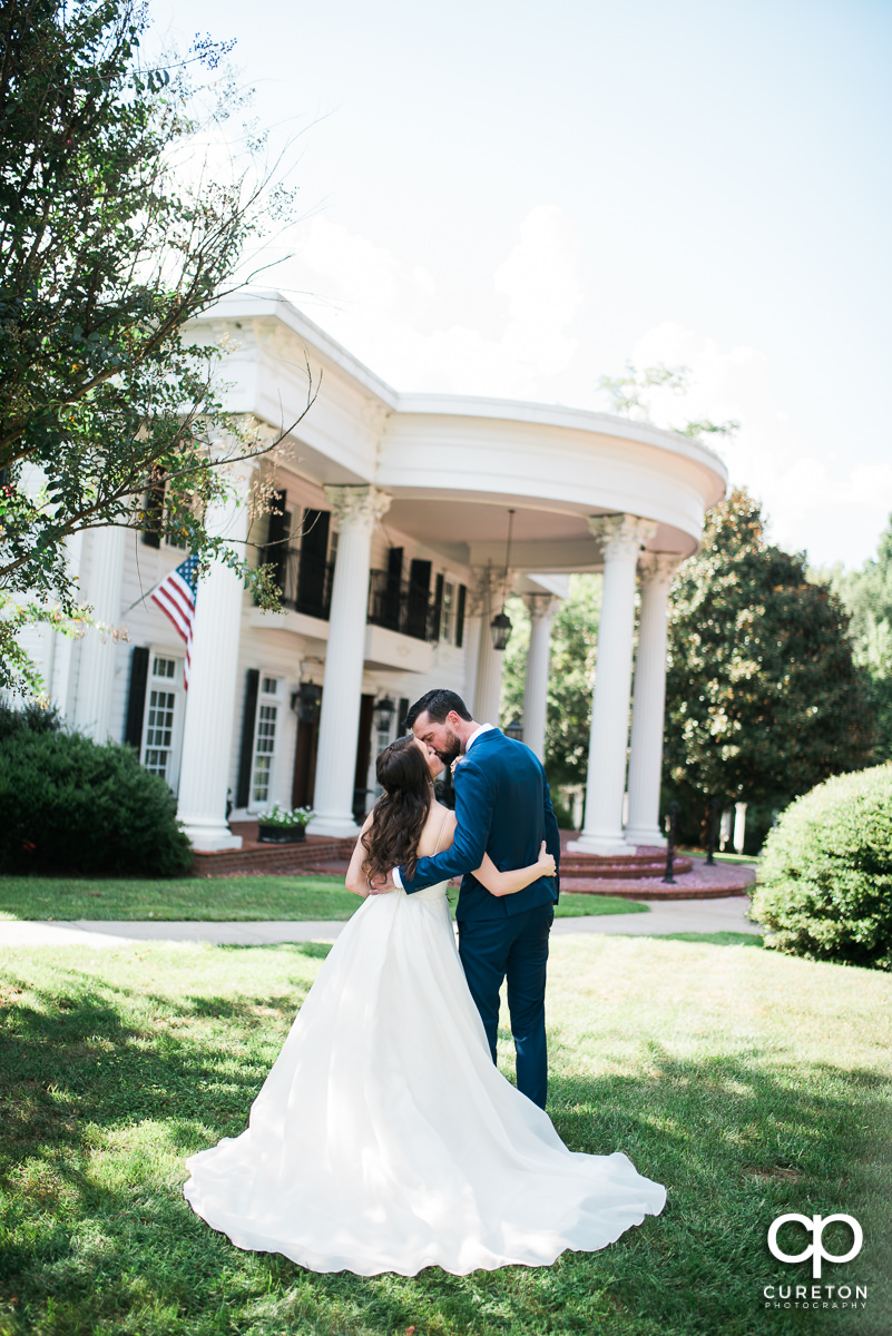Groom kissing his bride in front of the Southern mansion before their Ryan Nicholas Inn wedding in Mauldin,SC.