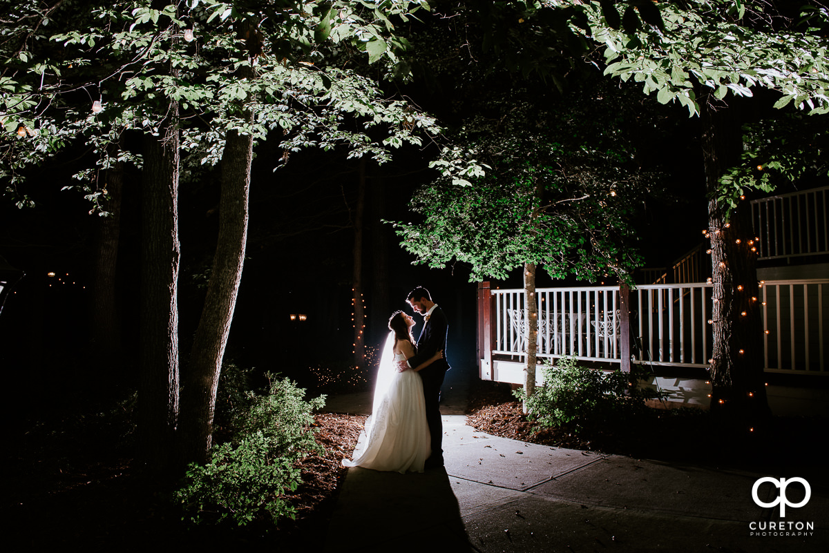 Bride and groom backlit in the garden at night after their Ryan Nicholas Inn wedding.